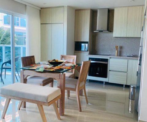 vista de zona comedor con mesa en madera y vidrio para 4 personas, en el fondo se ve una cocina abierta de estilo moderno