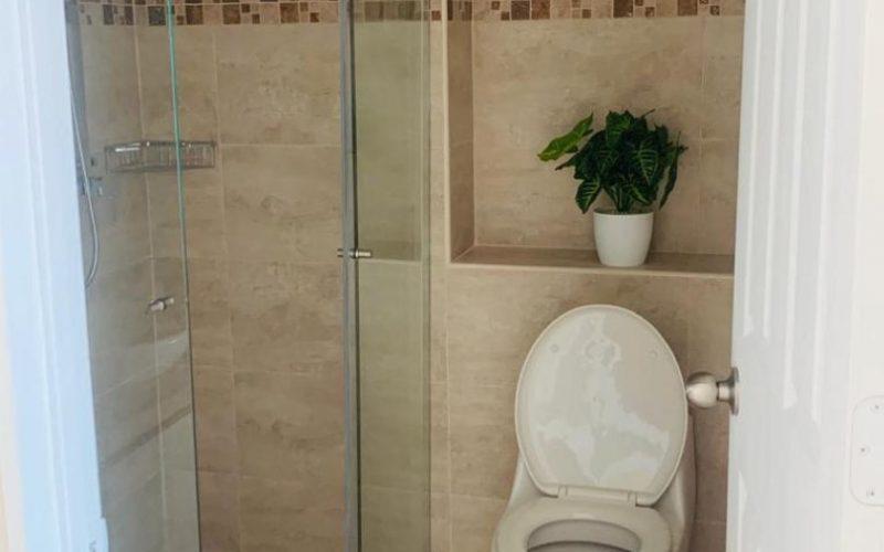 detalle de baño pequeño totalmente enchapado, con sanitario tradicional y ducha con divisiones en vidrio