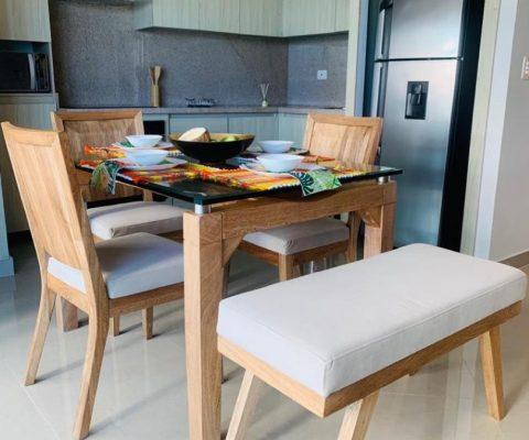detalle de mesa comedor en madera y vidrio con 3 sillas y una butaca; al fondo acompaña una cocina abierta de estilo moderno