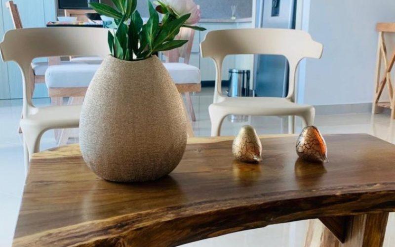detalle de mesa de café en madera con estilo rústico en el fondo se ve una cocina abierta elegante en colores claros