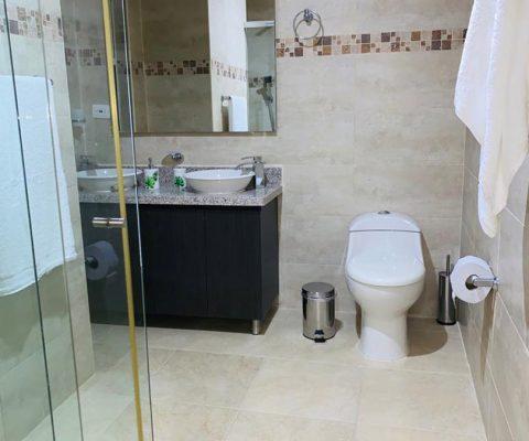 baño elegante y espacioso con sanitario moderno, mueble de lavamanos doble y enchapes en color arena