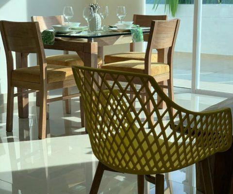 detalle de silla auxiliar estilo malla y en el fondo un comedor en madera para 4 personas. un ventanal da salida a un balcón
