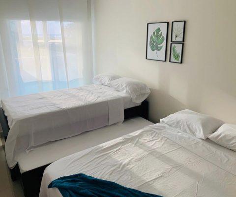 habitación equipada con cama doble y cama sencilla con función de nido en la parte inferior, la ventana tiene cortina cerrada