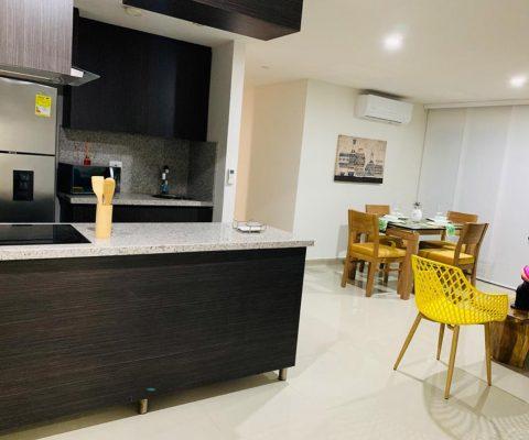 vista general de apartamento con cocina abierta de estilo elegante, sala de estar y comedor en madera para 4 personas