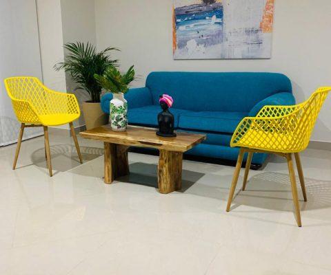sala de estar con sillas modernas tipo malla, sofá acolchado y mesa en madera de tipo rústico
