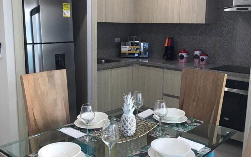 comedor elegante en madera y vidrio para 4 personas, al fondo una cocina abierta de estilo moderno en colores claros y grises