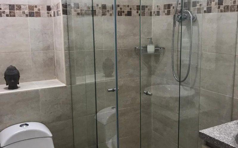 detalle de sanitario y ducha con divisiones en vidrio, de baño totalmente enchapado en color piedra