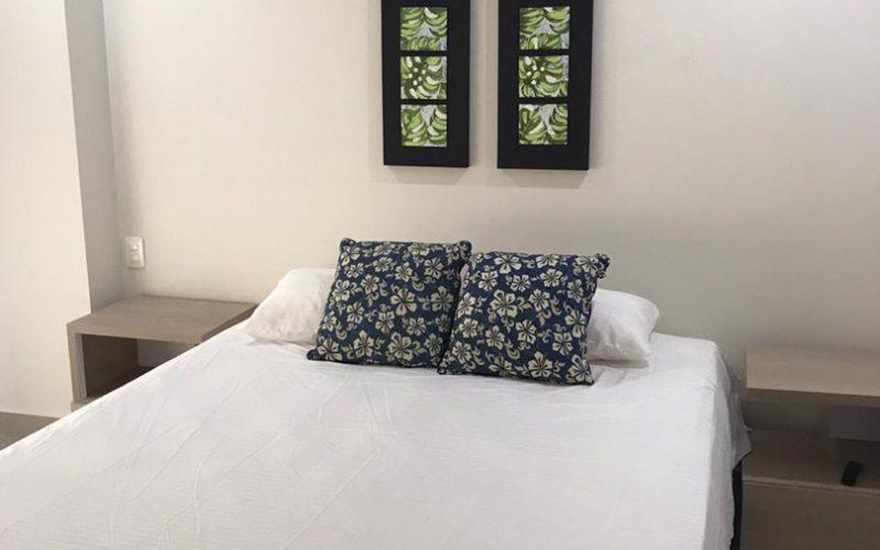 cama doble acompañada de 2 nocheros de estilo moderno y color claro en habitación de decoración simple