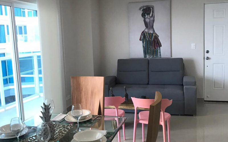 vista general de comedor y sala de estar en apartamento con decoración elegante, y ventanal piso techo que lleva a un balcón