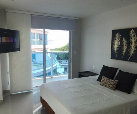 amplia habitación equipada con cama doble y tv, tiene salida por puerta ventana a balcón con vista a zona social del edificio