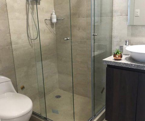 baño elegante con lavamanos de sobreponer en porcelana, sanitario y ducha de divisiones en vidrio, totalmente enchapado