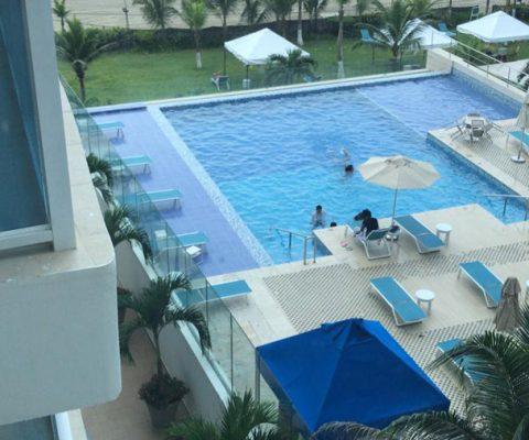 vista aérea de piscina de edificio, con jardín de palmeras y vista hacia una de las playas de Cartagena
