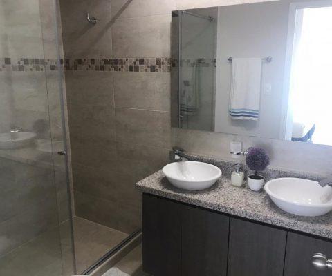 vista de baño elegante totalmente enchapado, con doble lavamanos, grifería moderna y ducha con divisiones en vidrio
