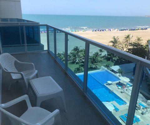 desde un balcón abajo se ve una piscina, un jardín de palmeras y en el fondo una de las playas de Cartagena