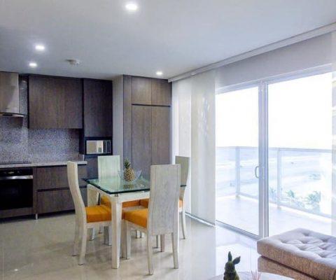 zona comedor con mesa y sillas para 4 personas, cocina abierta estilo moderno y amplio balcón con vista al mar de Cartagena