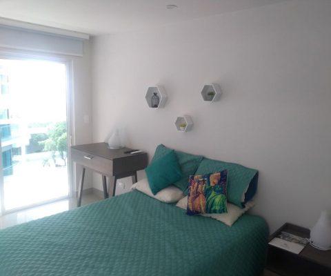 habitación con ventana piso techo de vista exterior, equipada con cama doble, nochero y mesa auxiliar