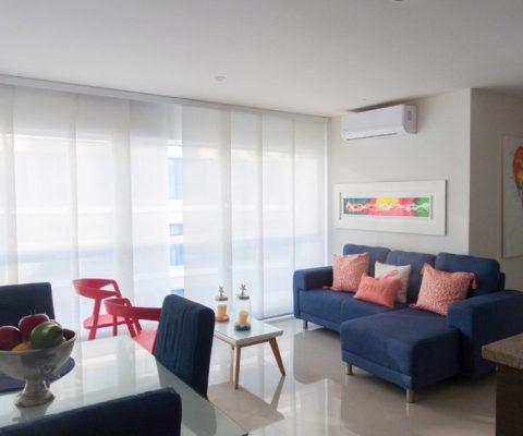 zona comedor para 3 personas y sala de estar equipada con sofá en L y mesa de café, ventanal piso techo de gran luminosidad