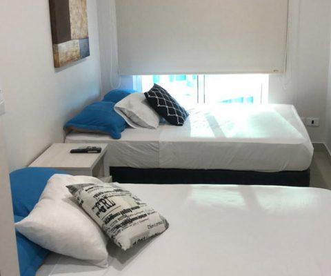amplia habitación en apartamento para alquiler,equipada con 2 camas dobles y nochero de estilo moderno