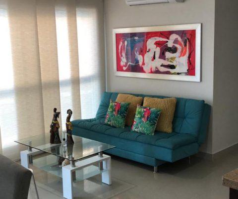 sala de estar en apartamento para alquiler en Cartagena, equipada con sofacama y mesa de café en vidrio y metal