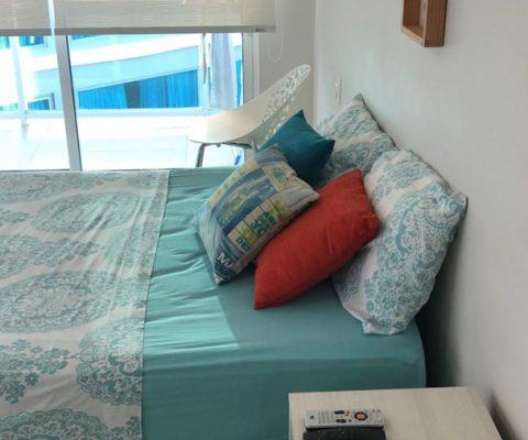 habitación amplia, equipada con cama doble, nochero sencillo y silla auxiliar. su ventana tiene vista al edificio vecino