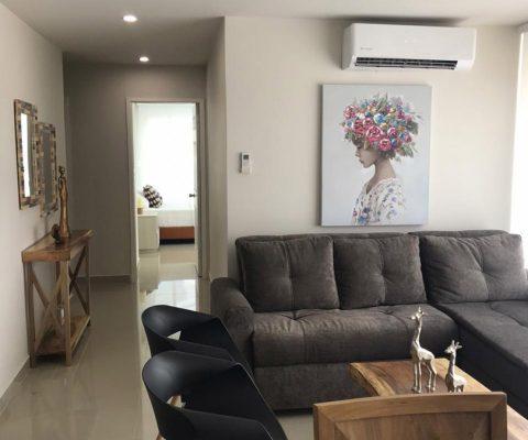 sala de estar con sofá en L, sillas auxiliares y mesa de café, junto a pasillo que lleva a habitación con cama y nochero