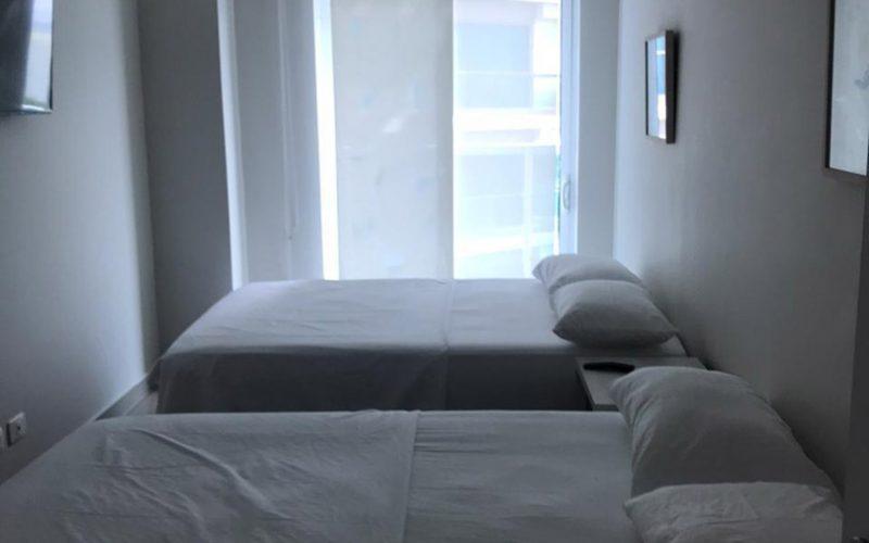 habitación equipada con 2 camas dobles, nochero y tv en pared, su ventana de piso a techo con cortina estilo panel japonés