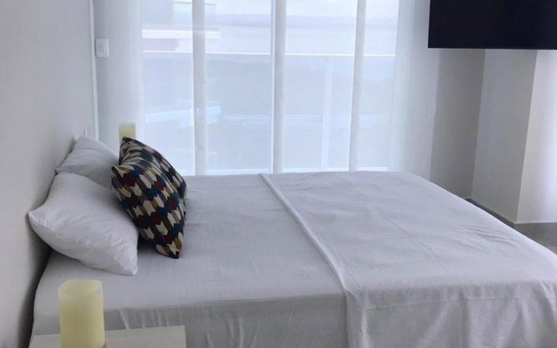 habitación amplia equipada con cama doble y nocheros modernos, su ventana de piso a techo con cortina estilo panel japonés