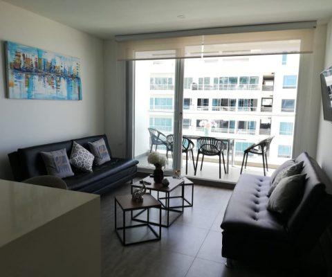 sala de estar y balcón en apartamento de Cartagena, ambos espacios decorados con mobiliario de estilo moderno