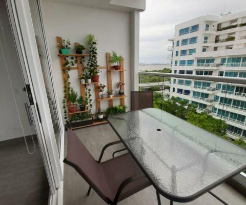 balcón amoblado con sillas y mesa metálicas, y jardín vertical en apartamento de la Zona Norte de Cartagena