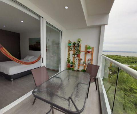 desde el balcón de un apartamento en Cartagena se puede ver la habitación principal equipada con cama doble y hamaca