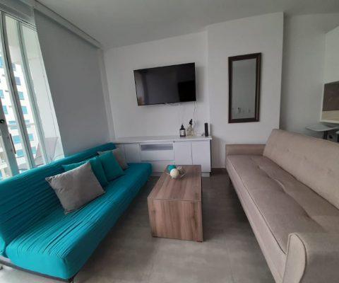 sala de estar con 2 sofás, mesa de café y tv en la pared en apartamento de la Zona Norte de Cartagena