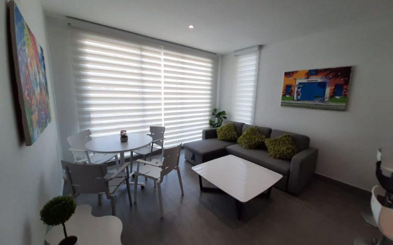 área de sala comedor con mobiliario de diseño, mesa para 4 y sofá en L, en apartamento para alquiler en Cartagena
