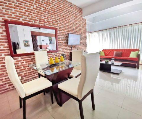 moderno espacio de sala comedor con ladrillo a la vista en apartamento de la zona Laguito de Cartagena