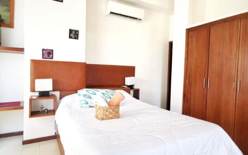 elegante habitación en apartamento para alquiler en Cartagena, equipada con cama doble, nocheros y abanico de techo