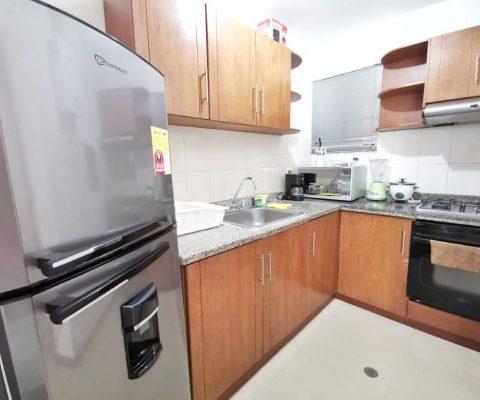 cocina abierta con muebles en madera y equipamento completo de línea blanca en apartamento para alquiler en Cartagena