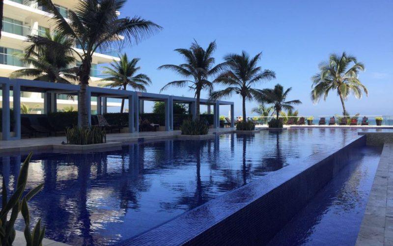 piscina sin fin rodeada de palmeras al frente de la playa de morros en cartagena