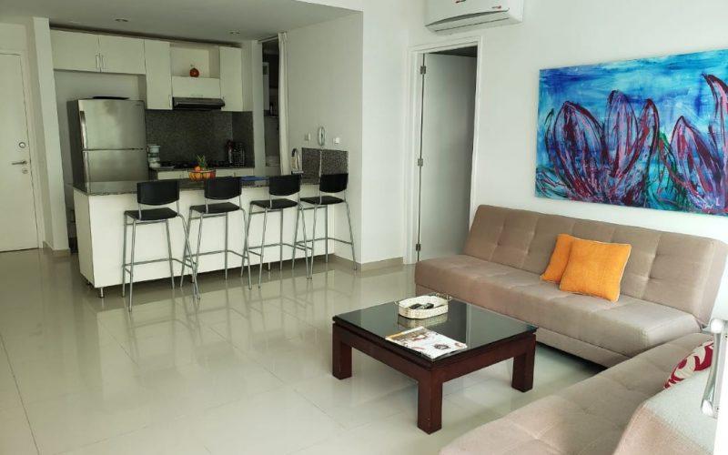 sala con dos sofacamas beige y mesa de madera cafe al fondo cocina tipo americana en apartamento en edificio morros ultra