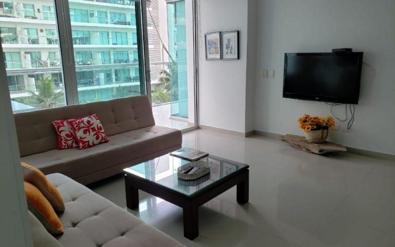 sala con dos sofas beige y televisor en la pared en aparatmento para alquilar por dias en morros ultra