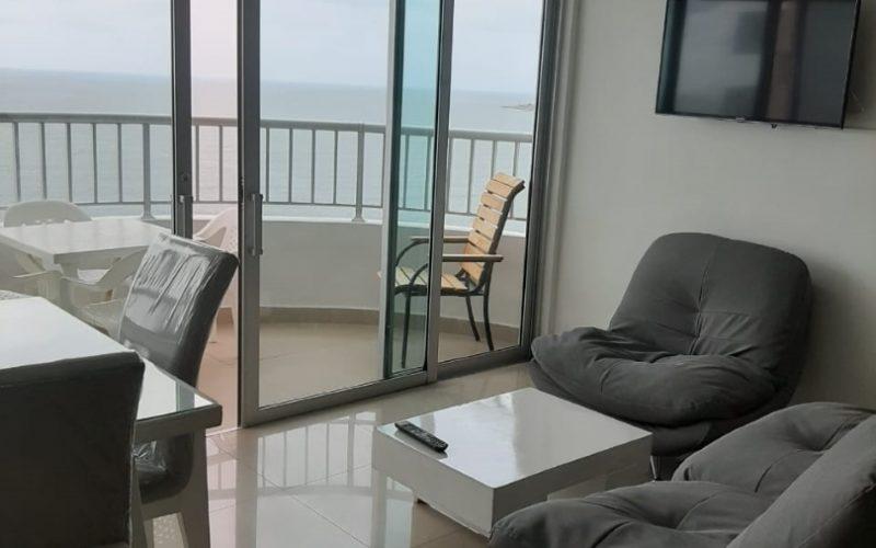 sala de estar en apartamento de Cartagena con sofá, poltrona, mesa de café y salida a balcón amoblado con vista al mar