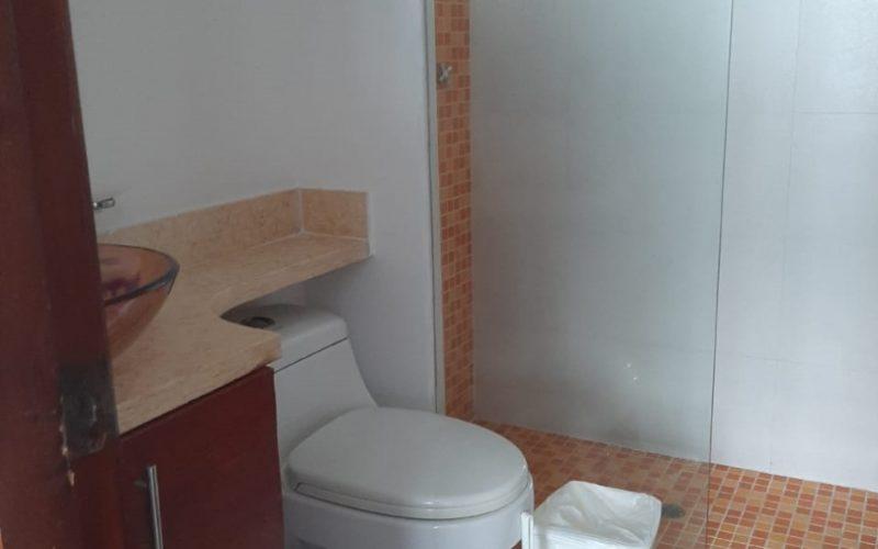 baño con lavamanos en vidrio sobre encimera de piedra, sanitario y ducha enchapada en azulejos naranjas