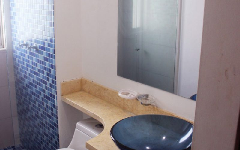 baño con lavamanos de vidrio sobre encimera de piedra, sanitario y ducha enchapada en azulejos azules