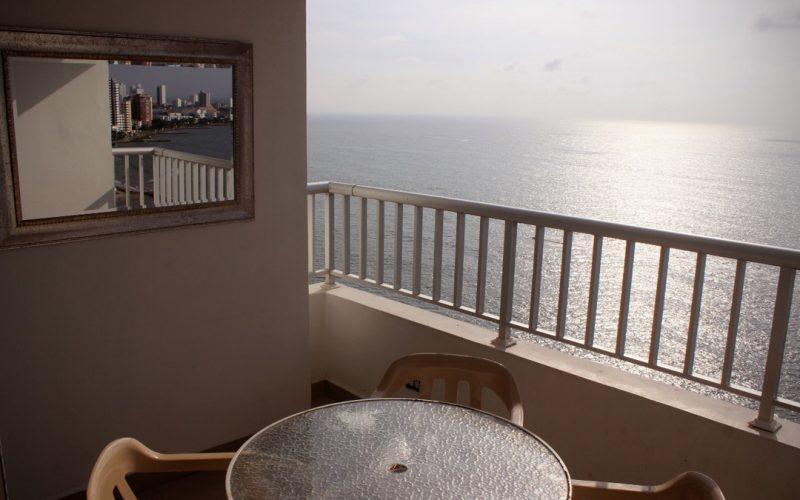 balcón con vista al mar y la ciudad de Cartagena, equipado con mesa redonda y sillas plásticas.