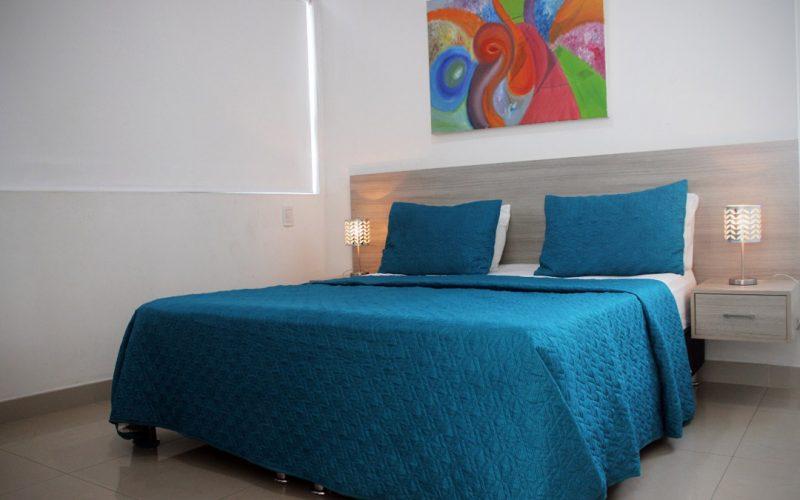 habitación con cama doble y cabecera de nocheros integrados, cuenta con una ventana que tiene la cortina cerrada