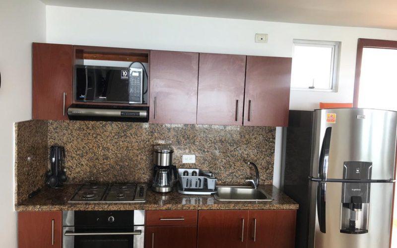 cocina tipo americano en colores madera y arena equipada con línea blanca en colores metálicos