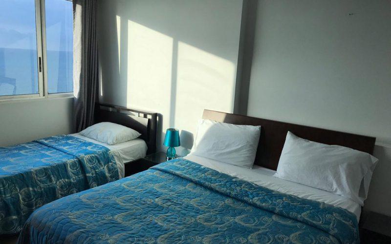 habitación equipada con cama doble, cama sencilla y un nochero tiene una ventana pequeña que da vista al mar de Cartagena