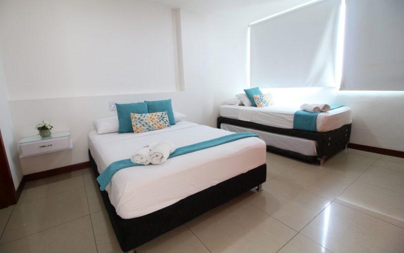 vista de frente de habitacion con una cama sencilla y una cama doble con ventana cubierta por blackout