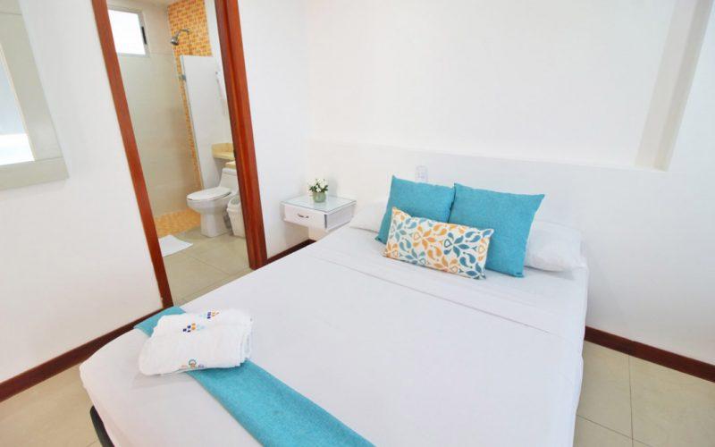 vista desde habitacion con cama sencilla a baño con azulejos naranja