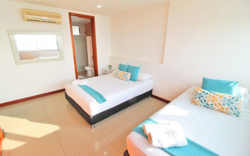 habitacion con dos camas sencillas con sabanas blancas y cobertor azul aguamarina