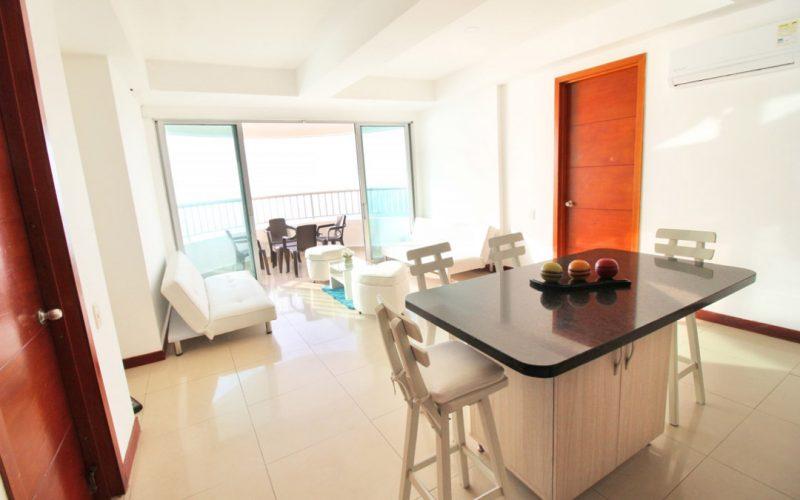 zona social de apartamento en alquiler cartagena con comedor con sillas altas sala con sillas blancas y comedor en balcon