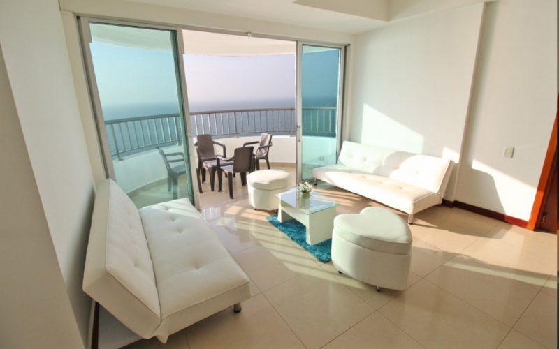 sala amoblada con sillas blancas de material cuero con un balcon en frente con vista al mar de cartagena
